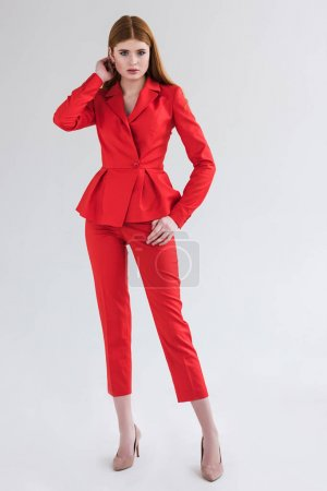 Female fashion model dressed in red formal suit isolated on grey
