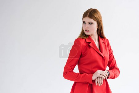 Young female fashion model with wristwatch dressed in jacket isolated on grey
