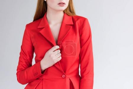 Cropped view of female fashion model in jacket isolated on grey