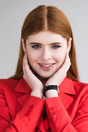 Portrait of smiling young female model with wristwatch isolated on grey