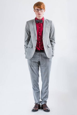 Male fashion model in eyeglasses dressed in suit and bow tie isolated on grey