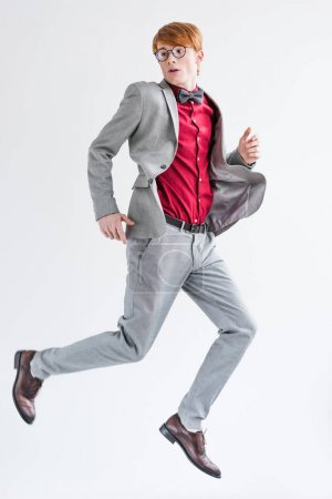 Jumping male fashion model dressed in suit isolated on grey