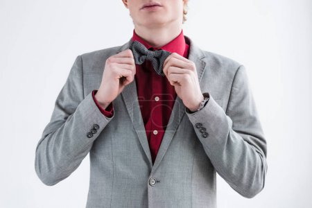 Cropped view of male fashion model adjusting bow tie isolated on grey