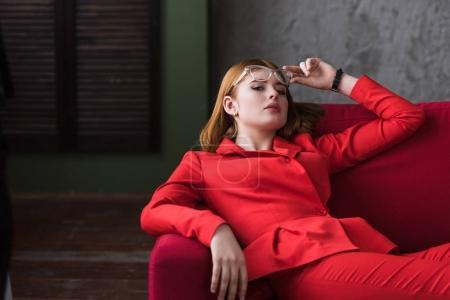 Élégante jeune femme enlever lunettes et couché sur le canapé
