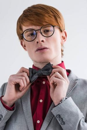 Low angle view of male fashion model in eyeglasses adjusting bow tie isolated on grey