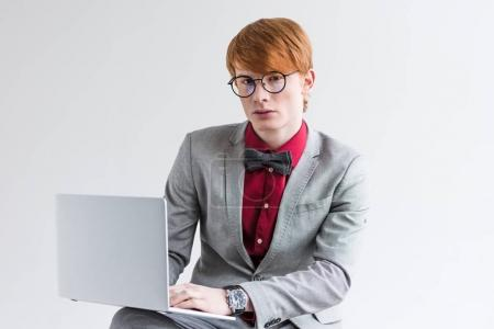 Young male fashion model in eyeglasses using laptop isolated on grey
