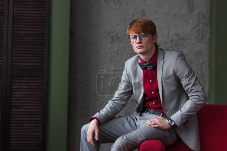 Male fashion model in eyeglasses dressed in grey suit