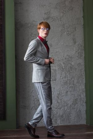 Young male fashion model in eyeglassed dressed in grey suit