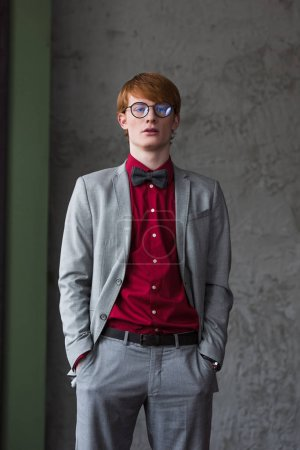 Young man in eyeglasses dressed in suit with bow tie