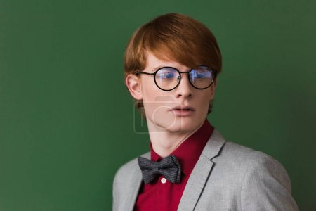 Young male fashion model in eyeglasses isolated on green