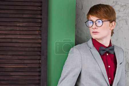 Male fashion model in eyeglasses standing in front of wall