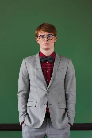 Young male fashion model in eyeglasses dressed in suit