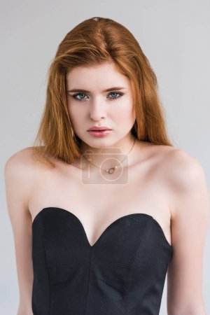 Portrait of female fashion model with necklace in dress isolated on grey