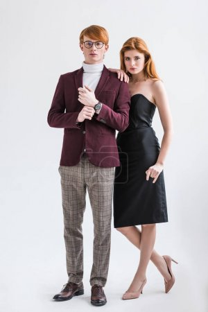 Photo for Male fashion model adjusting wristwatch while young female standing beside isolated on grey - Royalty Free Image
