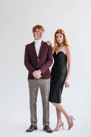 Young couple of fashion models dressed in formal wear isolated on grey