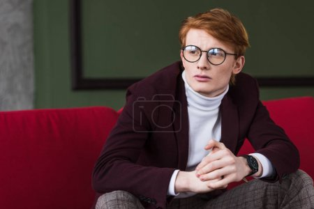 Young male fashion model in eyeglasses sitting on couch