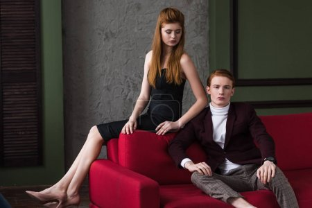Young couple of fashion models dressed in formal wear on couch