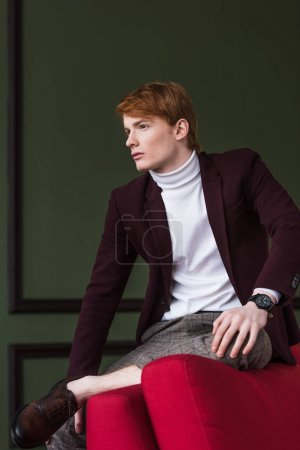 Side view of young male fashion model sitting on edge of couch