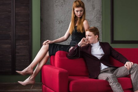 Attractive young stylish couple of models in formal wear on couch