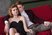 Young female fashion model with earrings and necklace sitting with boyfriend on couch