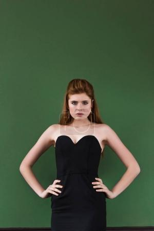 Female fashion model with earrings in dress on green