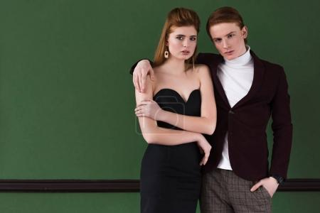 Young male fashion model holding girlfriend shoulder in front of wall