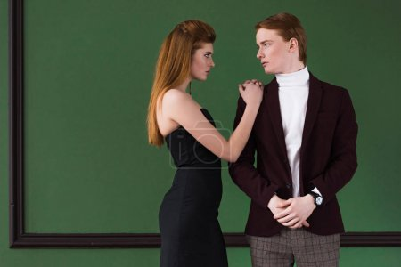 Side view of stylish young couple of models dressed in formal wear