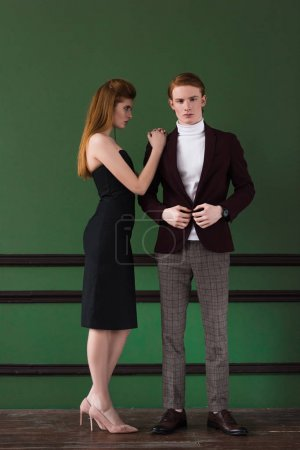 Photo for Stylish young female model in black dress with boyfriend in front of wall - Royalty Free Image