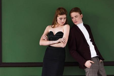 Stylish young couple dressed in formal wear in front of green wall