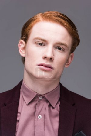 Portrait of male fashion model dressed in jacket isolated on grey
