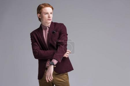Young stylish man dressed in jacket isolated on grey