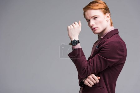 Young male fashion model with wristwach isolated on grey