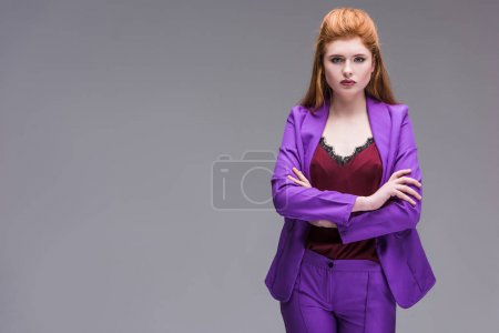 Young stylish female model dressed in purple suit isolated on grey
