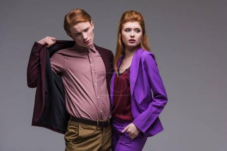 Couple of young fashion models dressed in formal wear isolated on grey