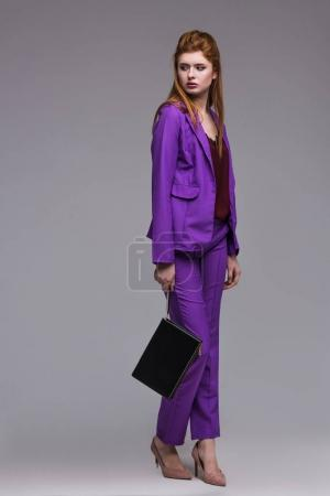 Young female fashion model in suit holding hanbag isolated on grey