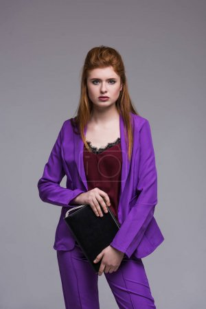 Photo for Female fashion model dressed in suit holding handbag isolated on grey - Royalty Free Image