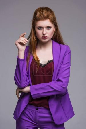 Portrait of stylish young female model in jacket isolated on grey