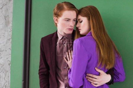 Young stylish male model holding girlfriend waist