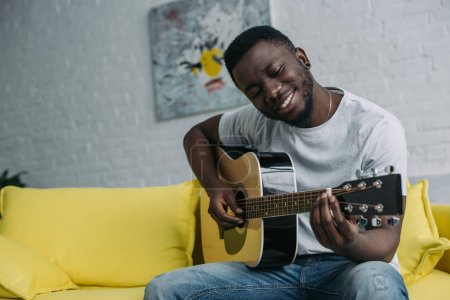 handsome smiling young african american man playing guitar at home