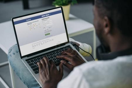 Schnappschuss eines jungen afrikanisch-amerikanischen Mannes mit Laptop und Facebook-Website auf dem Bildschirm