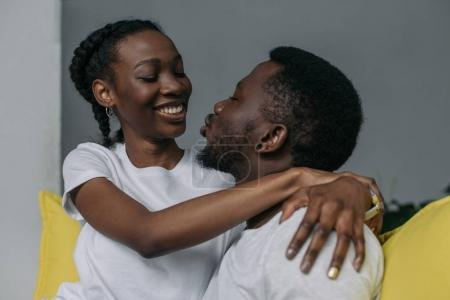 beautiful young african american couple hugging and smiling each other at home