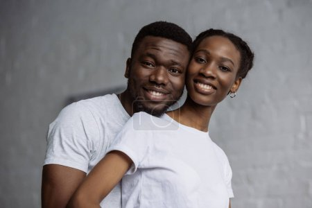 Photo for Happy young african american couple in white t-shirts smiling at camera - Royalty Free Image
