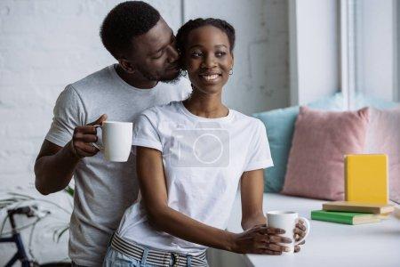 heureux jeune couple afro-américain boire du café ensemble à la maison