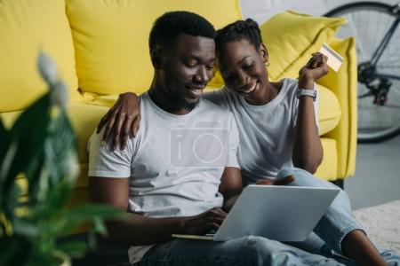 happy young african american couple with laptop and credit card shopping online together