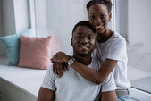 happy young african american couple in white t-shirts smiling at camera at home