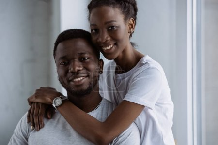 happy young african american couple in white t-shirts hugging and smiling at camera