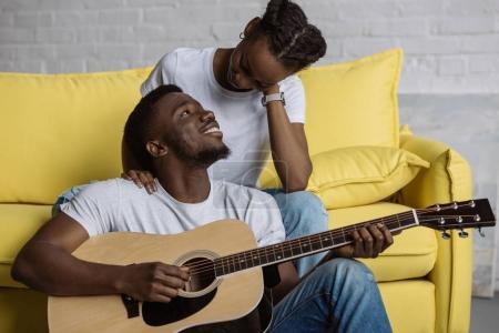 Photo pour Beau sourire de jouer de la guitare jeune homme et regardant la belle copine à la maison - image libre de droit