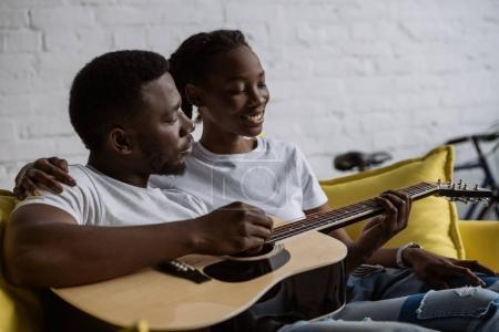 Foto de Feliz pareja afroamericana joven sentados juntos en el sofá y hombre tocando guitarra acústica - Imagen libre de derechos