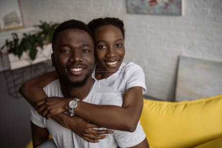 happy young african american couple hugging and smiling at camera