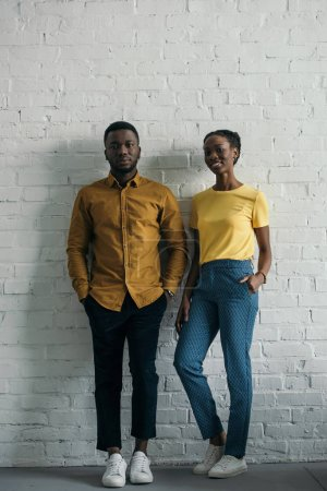 beautiful smiling young african american couple in yellow shirt and t-shirt looking at camera